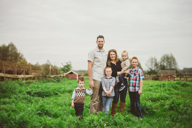 Young family posing for family portrait in farmers field